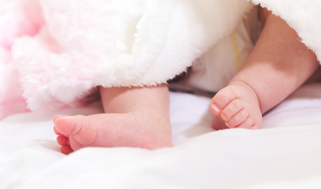 baby's feet: Newborn infant babys feet sticking out from under her blanket