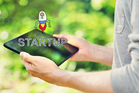 tablet pc in hand: Startup concept with young man holding his tablet computer outside in the park Stock Photo