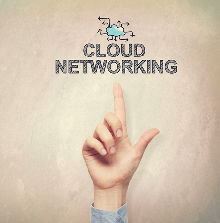 wall cloud: Hand pointing to Cloud Networking concept on light brown wall background Stock Photo