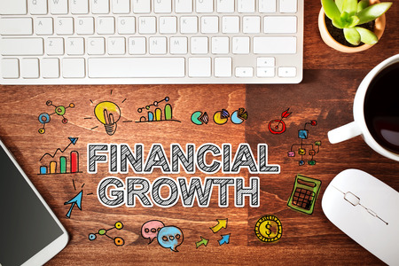 financial growth: Financial Growth concept with workstation on a wooden desk