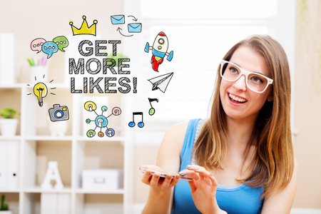 woman smartphone: Get more likes concept with young woman wearing white glasses using her smartphone in her home Stock Photo