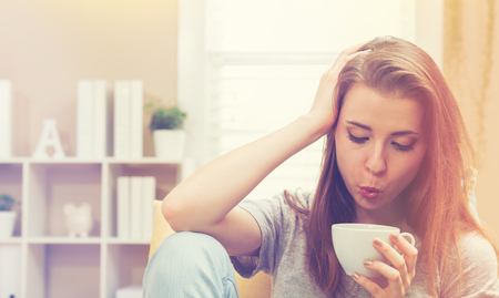 couch: Young woman drinking coffee on her couch at home Stock Photo
