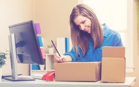 젊은 여자가 그녀의 본사에 배송 상자를 포장