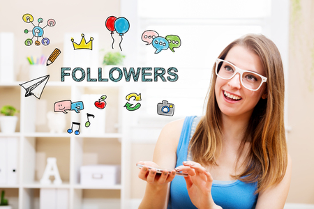 Followers concept with young woman wearing white glasses using her smartphone in her home