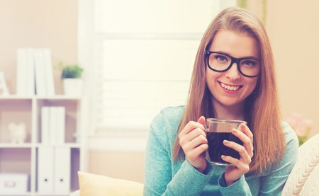 couch: Happy young woman drinking coffee on her couch at home