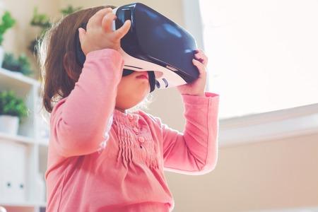 Muchacha del niño utilizando un nuevo casco de realidad virtual Foto de archivo - 58705924
