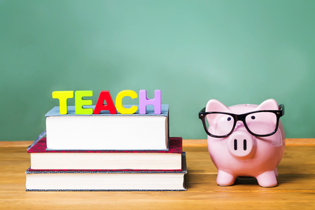 scholarship: Teaching theme with pink piggy on top of books with chalkboard in the background as concept image of the costs of education