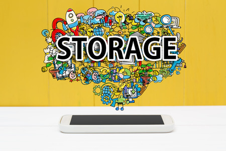 storage: Storage concept with smartphone on yellow wooden background