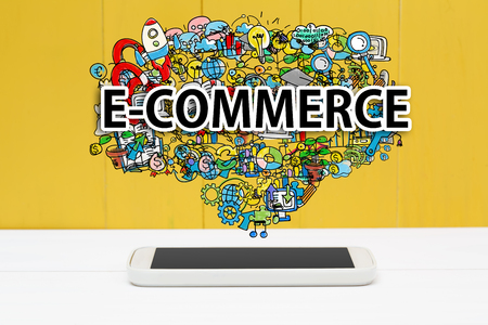 digital marketing: E-Commerce concept with smartphone on yellow wooden background
