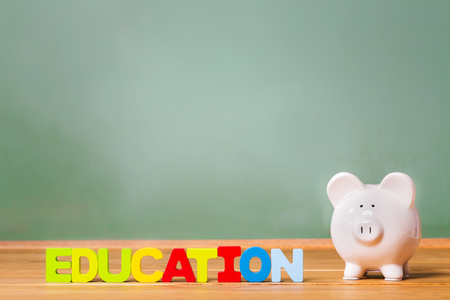 Bildung Thema mit weiß Sparschwein und grüne Tafel Hintergrund Standard-Bild - 58705391