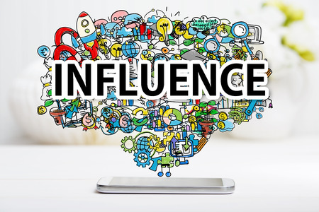 influence: Influence concept with smartphone on white table Stock Photo