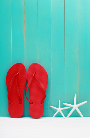 flops: Flip Flops and starfish on teal wooden background Stock Photo