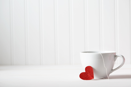 coffee table: Coffee cup with small heart on white wooden background