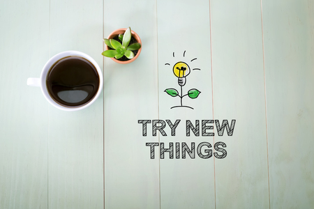 to try: Try New Things concept with a cup of coffee on a pastel green wooden table