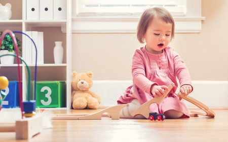 babies playing: Happy toddler girl playing with toys in her house