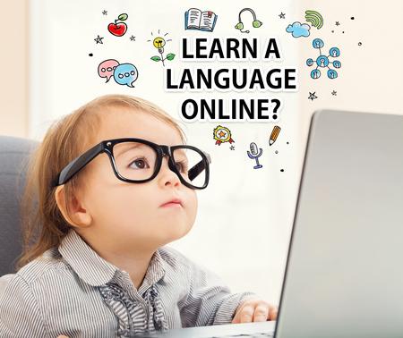 Un concepto de aprender idiomas online con la muchacha del niño con su ordenador portátil Foto de archivo - 59198778
