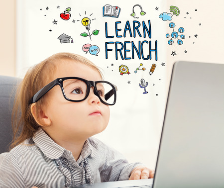 Learn French concept with toddler girl using her laptop