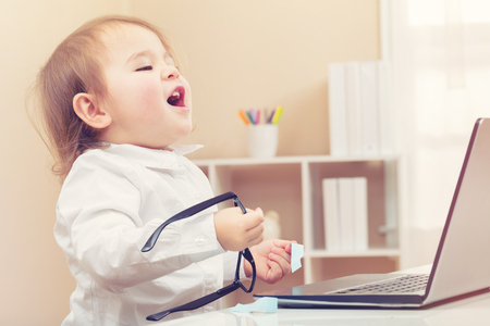 laptop home: Happy toddler girl laughing while using her laptop in her house