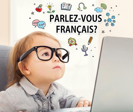 Parlez vous Francais (¿Habla francés) textos con la muchacha del niño que usa su computadora portátil Foto de archivo - 59198824