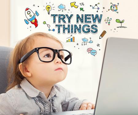 Essayer de nouvelles choses avec le concept tout-petit fille en utilisant son ordinateur portable Banque d'images