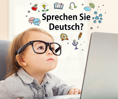 mixed race children: Sprechen Sie Deutsch (Do you speak German) texts with toddler girl using her laptop Stock Photo