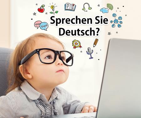 deutsch: Sprechen Sie Deutsch (Do you speak German) texts with toddler girl using her laptop Stock Photo