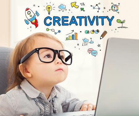 그녀의 노트북을 사용하는 유아 소녀와 창의력 개념
