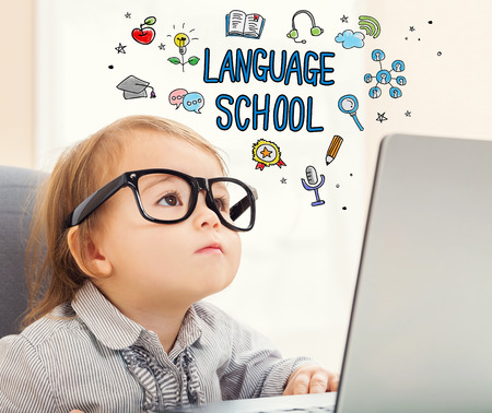 girl laptop: Language school concept with toddler girl using her laptop Stock Photo