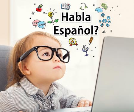 clases: Habla Español (¿Habla español) textos con la muchacha del niño que usa su computadora portátil Foto de archivo