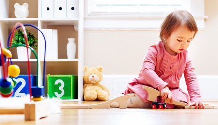 inside house: Happy toddler girl playing with toys in her house