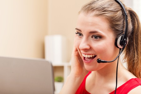 Caucasian woman: Happy young woman with headset talking on her laptop Stock Photo