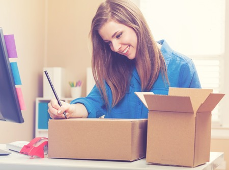 shipped: Young woman packing boxes to be shipped in her home office