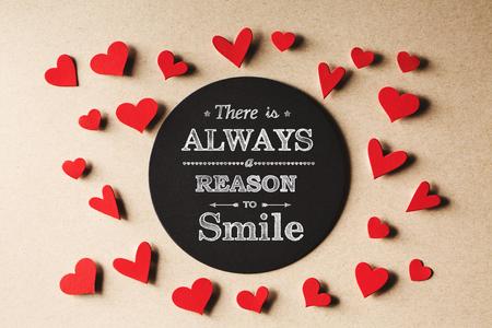 Er is altijd reden om bericht met handgemaakte kleine papieren harten glimlach Stockfoto