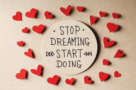 small paper: Stop Dreaming Start Doing message with small paper hearts Stock Photo