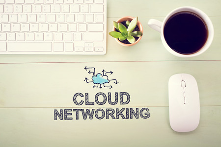 workstation: Cloud Networking concept with workstation on a light green wooden desk Stock Photo