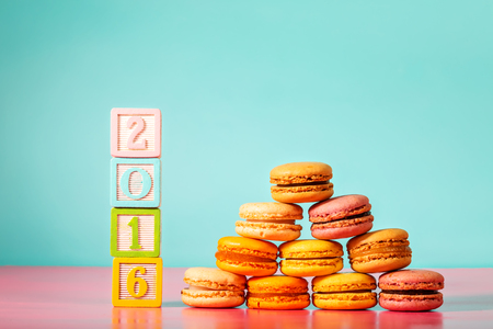 woodblock: Stack of macarons with 2016 woodblock numbers on pastel pink and blue background Stock Photo
