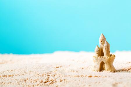 明るい青色の背景で砂の城の夏テーマ