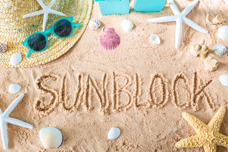 Sunblock text in the sand with beach accessories