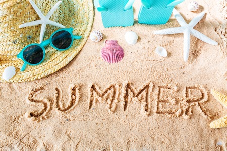 Summer text in the sand with beach accessories Stock Photo