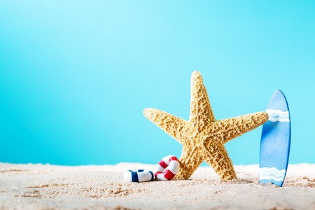 flotation: Summer theme with starfish and surfboard in the sand on a bright blue background