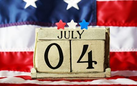 julio: El 4 de julio día el tema de la independencia americana con el calendario bloque de madera Foto de archivo