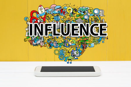 influence: Influence concept with smartphone on yellow wooden background Stock Photo