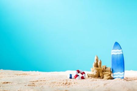밝은 파란색 배경에 서핑 보드와 모래 성 여름 테마