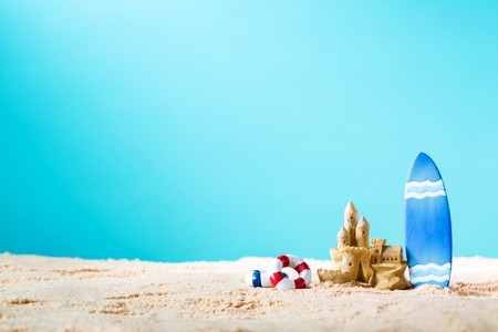 Zomer thema met surfplank en zandkasteel op een heldere blauwe achtergrond