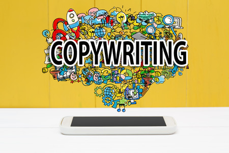 copywriting: Copywriting concept with smartphone on yellow wooden background