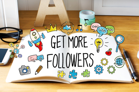 followers: Get More Followers concept with notebook on wooden desk