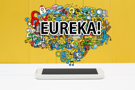 Eureka concept with smartphone on yellow wooden background