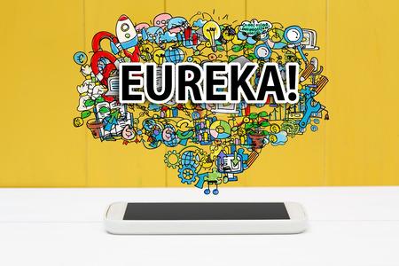 eureka: Eureka concept with smartphone on yellow wooden background Stock Photo