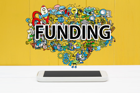funding: Funding concept with smartphone on yellow wooden background Stock Photo