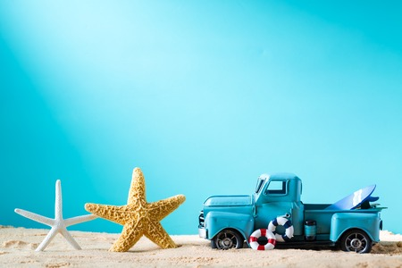 flotation: Miniature blue truck with surfboard and starfish on a bright blue background